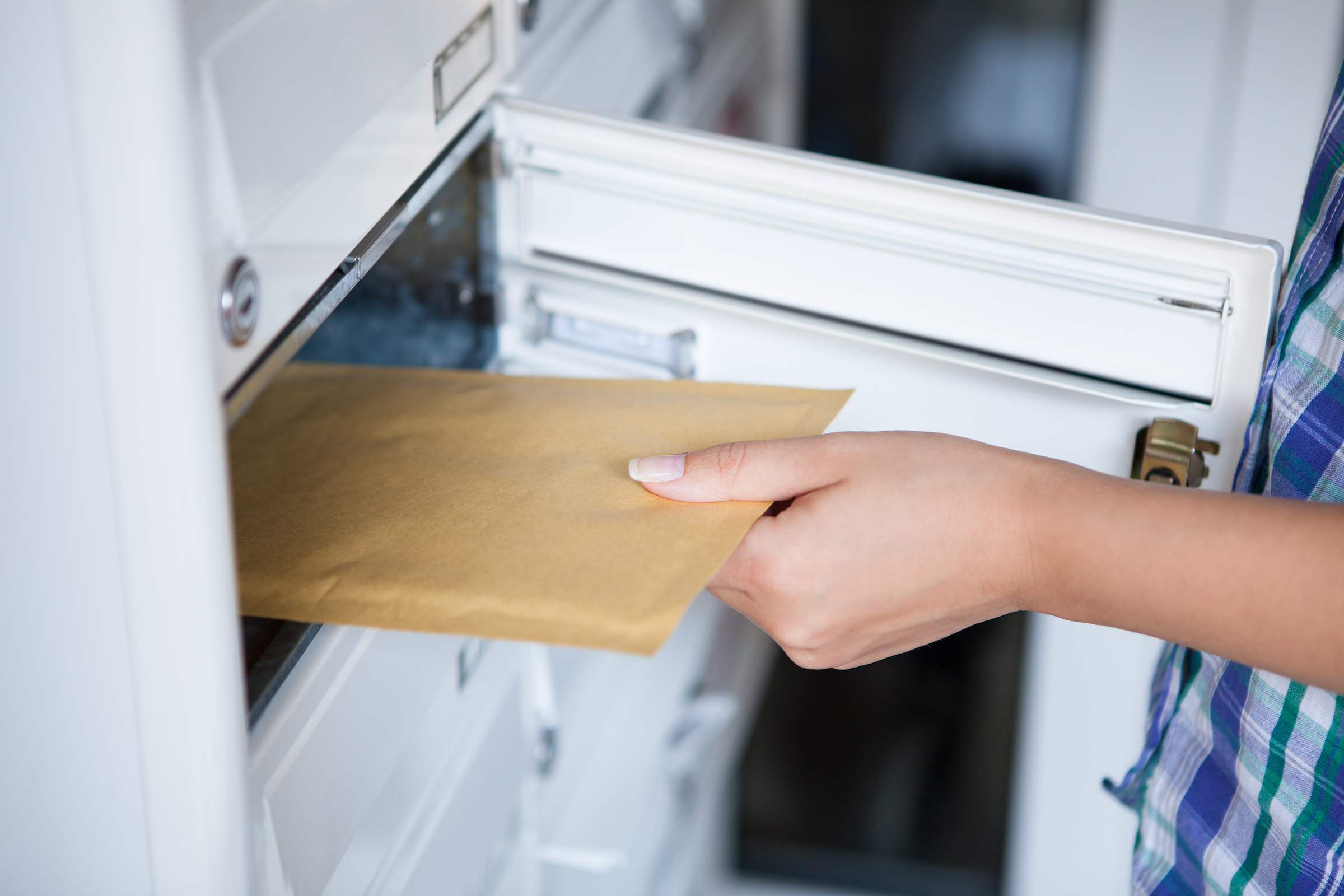 Woman opening a private postal distribution mailbox